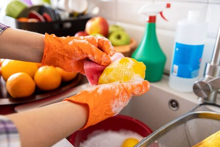 Washing fruits in the kitchen with water and soap