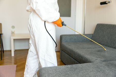 Person in protective suit with decontamination sprayer bottle disinfecting household and furniture