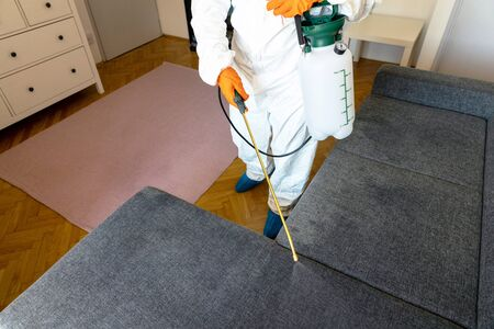 Person in protective suit with decontamination sprayer bottle disinfecting household and furniture 版權商用圖片
