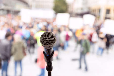 Public demonstration, street protest or political rally. Microphone in focus against unrecognizable crowd of people. 版權商用圖片