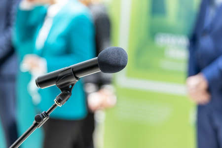 Microphone in focus against blurred people at news or press conference. Public relations - PR concept.