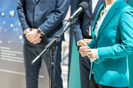 Business woman or female politician is giving a speech at media event