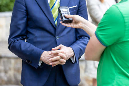 Journalist holding voice recorder making media interview with politician or business person