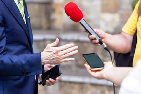 Reporter holding microphone making media interview with businessman or politician