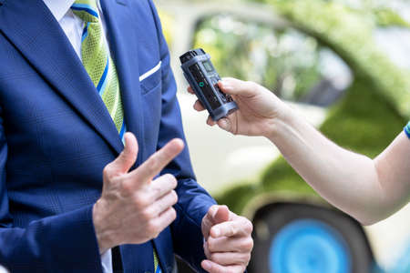 Reporter holding voice recorder making media interview with politician or business person 版權商用圖片