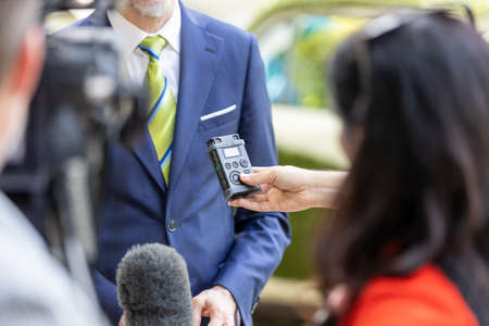 Journalists holding microphone and digital voice recorder during news conference or press briefing with business person
