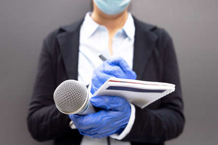 Journalist wearing protective gloves and face mask against COVID-19 disease holding microphone writing notes during virus pandemic