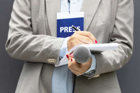Female journalist at news conference or media event, writing notes, holding microphone. Journalism concept