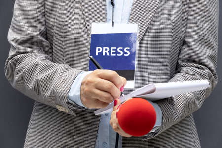 Female reporter at news conference or media event, writing notes, holding microphone. Journalism concept.