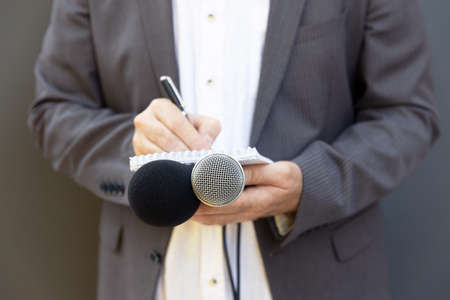 Journalist at news conference or media event, writing notes, holding microphone 免版税图像