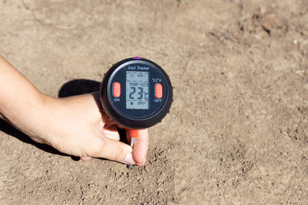 Soil temperature, moisture content, environmental humidity and illumination measurement. Global warming concept.