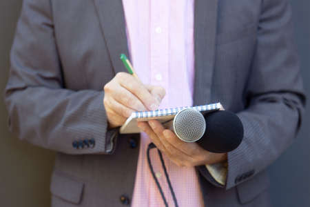 Reporter at press conference or media event, writing notes, holding microphone