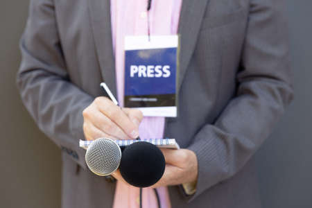 Journalist at news conference or media event, holding microphone, writing notes. Journalism concept.
