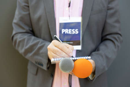 Journalist at press conference or media event, holding microphone, writing notes. Journalism concept.