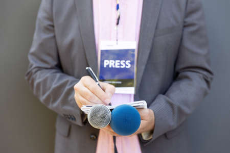 Male journalist at news conference or media event, holding microphone, writing notes. Journalism concept. 免版税图像