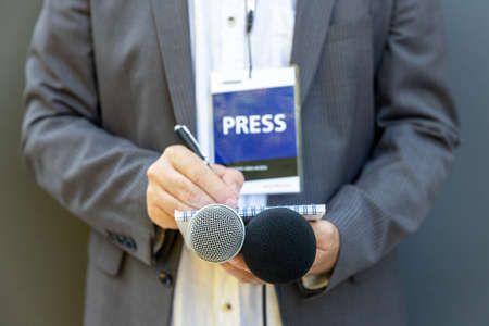 Male journalist at news conference or media event, writing notes, holding microphone 免版税图像