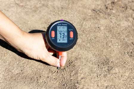 Soil temperature in the fahrenheit scale, moisture content, environmental humidity and illumination measurement. Global warming concept.