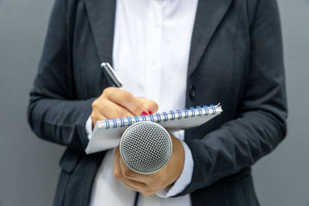 Female journalist at media event or news conference, writing notes, holding microphone. Journalism concept.