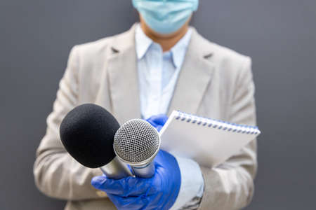 Female journalist wearing protective gloves and face mask against coronavirus COVID-19 disease holding microphone writing notes during virus pandemic