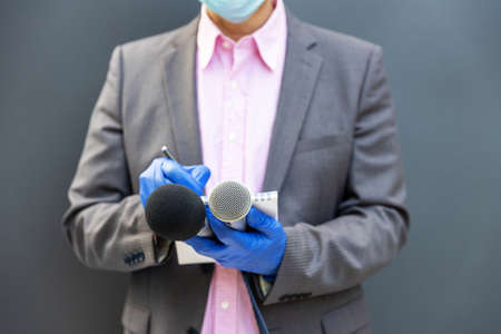 Journalist at news conference wearing protective gloves and face mask against coronavirus COVID-19