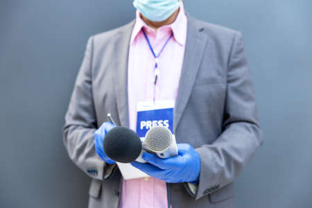 Journalist at news conference or media event wearing protective gloves and face mask against coronavirus COVID-19 disease holding microphone writing notes during virus pandemic 免版税图像