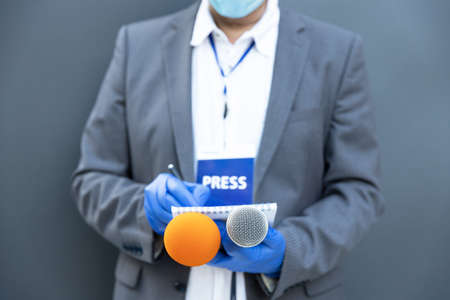 Journalist at news conference or media event wearing protective gloves and face mask against coronavirus COVID-19 disease holding microphone writing notes 免版税图像
