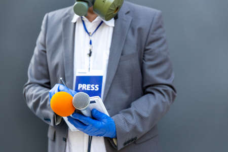 Reporter at press conference or media event wearing protective gloves and face mask against coronavirus COVID-19 disease holding microphone writing notes