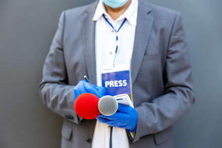 Journalist at news conference or media event wearing protective gloves and face mask against coronavirus COVID-19 disease 免版税图像
