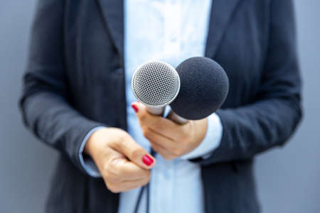 Television reporter holding microphone during press interview. Journalism concept.