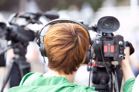 Camerawoman at work during news conference or media event filming with video camera Banco de Imagens