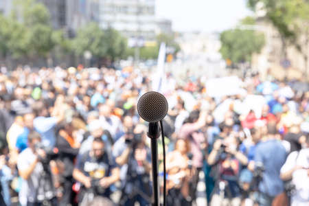 Focus on microphone, blurred group of people at mass protest in the background 免版税图像