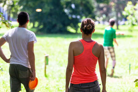 People playing flying disc golf sport game in the public park or nature