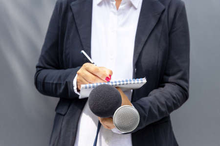 News reporter or TV journalist at press conference or media event, holding microphone and writing notes. Journalism concept.