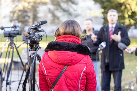 Shooting media event or news conference with a video camera. Public relations - PR concept.