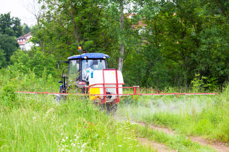 Pest control vehicle spraying insecticides or pesticides. Ragweed hay fever chemical treatment.