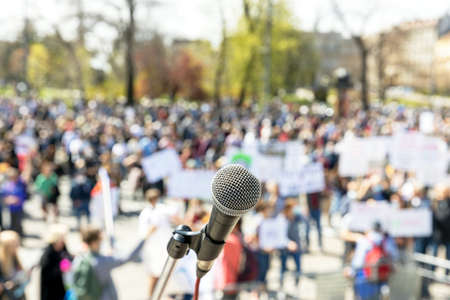 Protest or public demonstration, focus on microphone, blurred group of people in the background