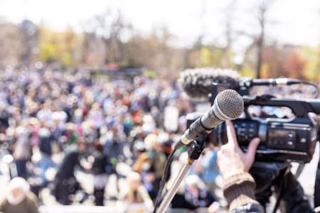 Filming protest or public demonstration, focus on microphone, blurred crowd of people in the background
