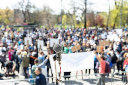 Protest or public demonstration, focus on microphone, blurred crowd of people in the background