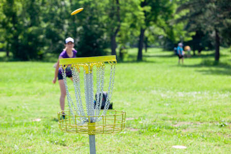 Young woman playing flying disc golf sport game in the nature 免版税图像