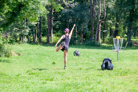 Young woman playing flying disc golf sport game in the park 免版税图像