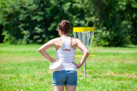 Young woman playing flying disc sport game in the nature 免版税图像