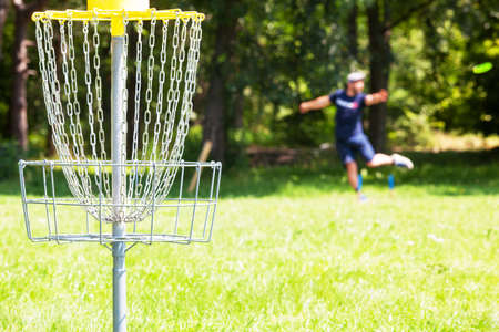 Man playing flying disc golf sport game in the city park or nature