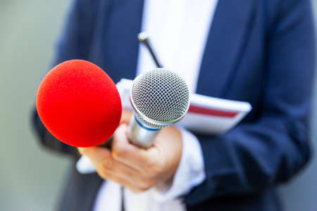 Microphone in focus, female reporter at news conference writing notes. Public relations (PR) concept.