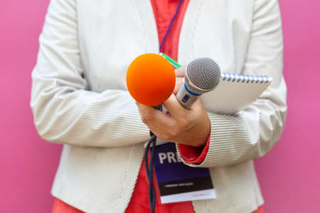 Microphone in focus, female journalist at press conference writing notes during awards ceremony