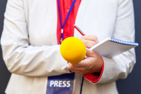 Female journalist or reporter at news conference or media event. Journalism concept.