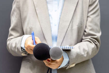 Female reporter at news conference or media event, writing notes, holding microphone