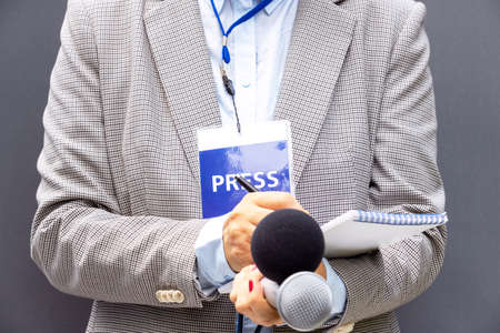Female reporter at press conference or media event, writing notes, holding microphone. Broadcast journalism concept.