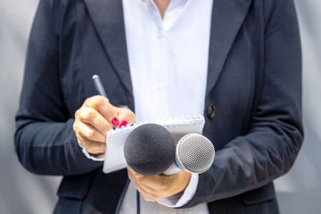 Journalist at news conference or media event, writing notes, holding microphone. Broadcast journalism concept.