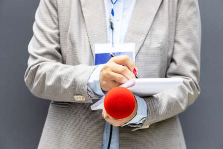 Reporter at press conference or media event, writing notes, holding microphone. Broadcast journalism concept. 免版税图像