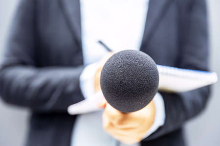 Journalist holding microphone at news conference or media event and writing notes